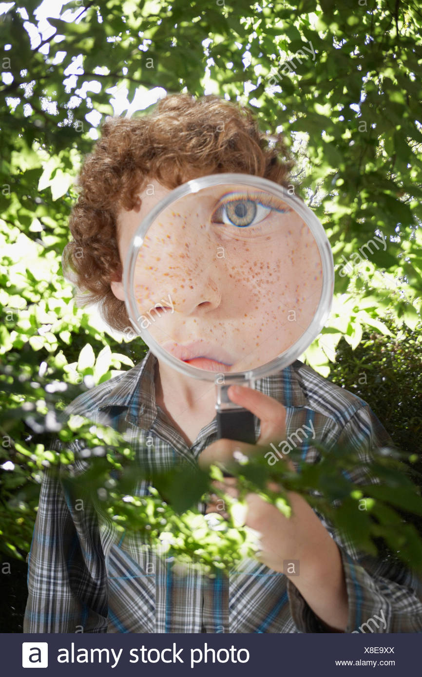 Young boy outdoors looking through a magnifying glass - Stock Image