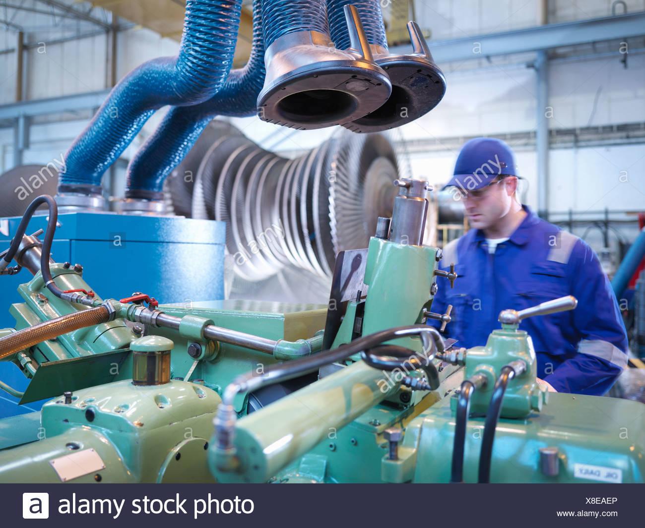 Engineer operating machinery in steam turbine repair workshop - Stock Image