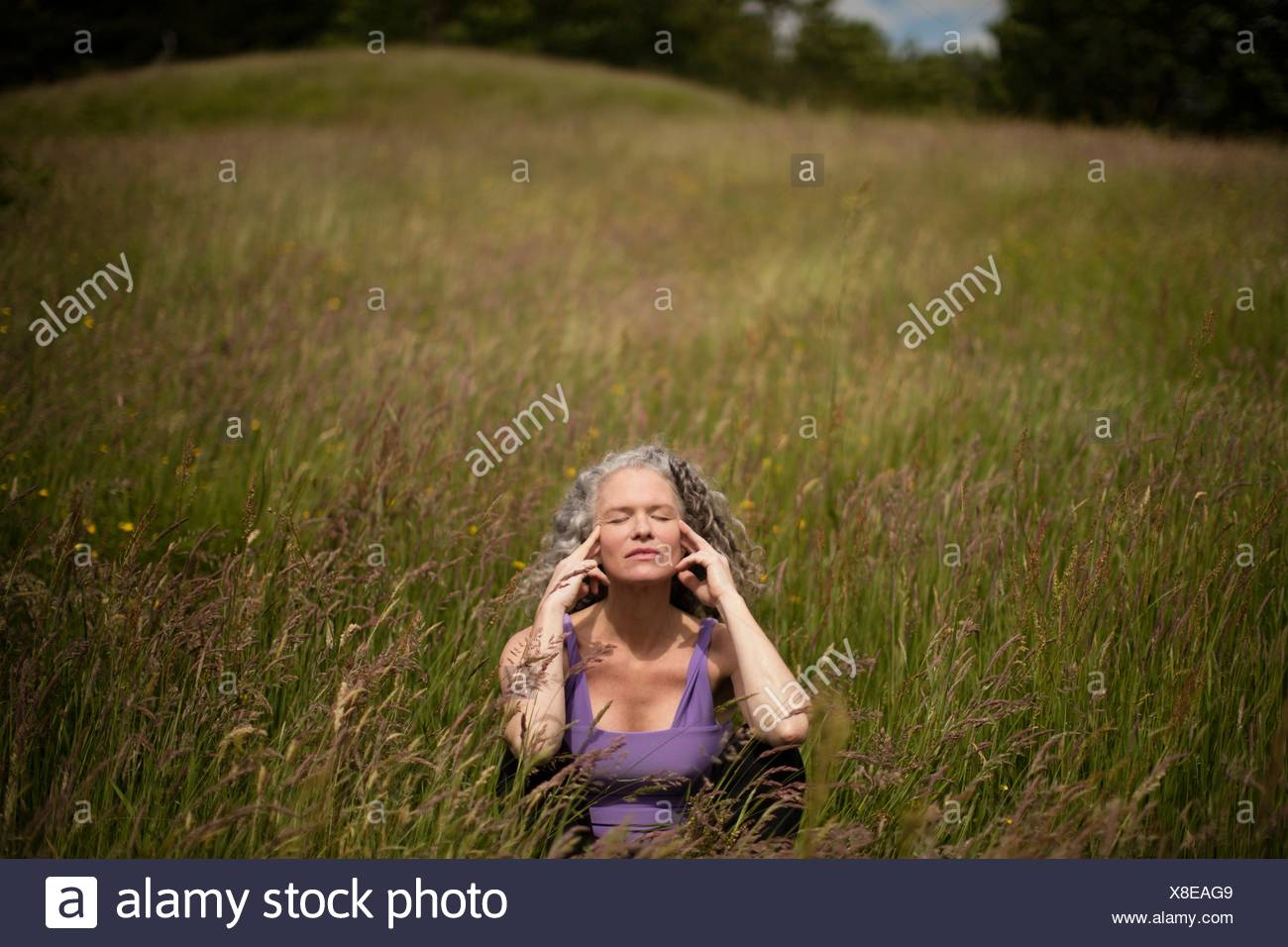 Mature woman with fingers on her temples sitting in long grass meditating - Stock Image