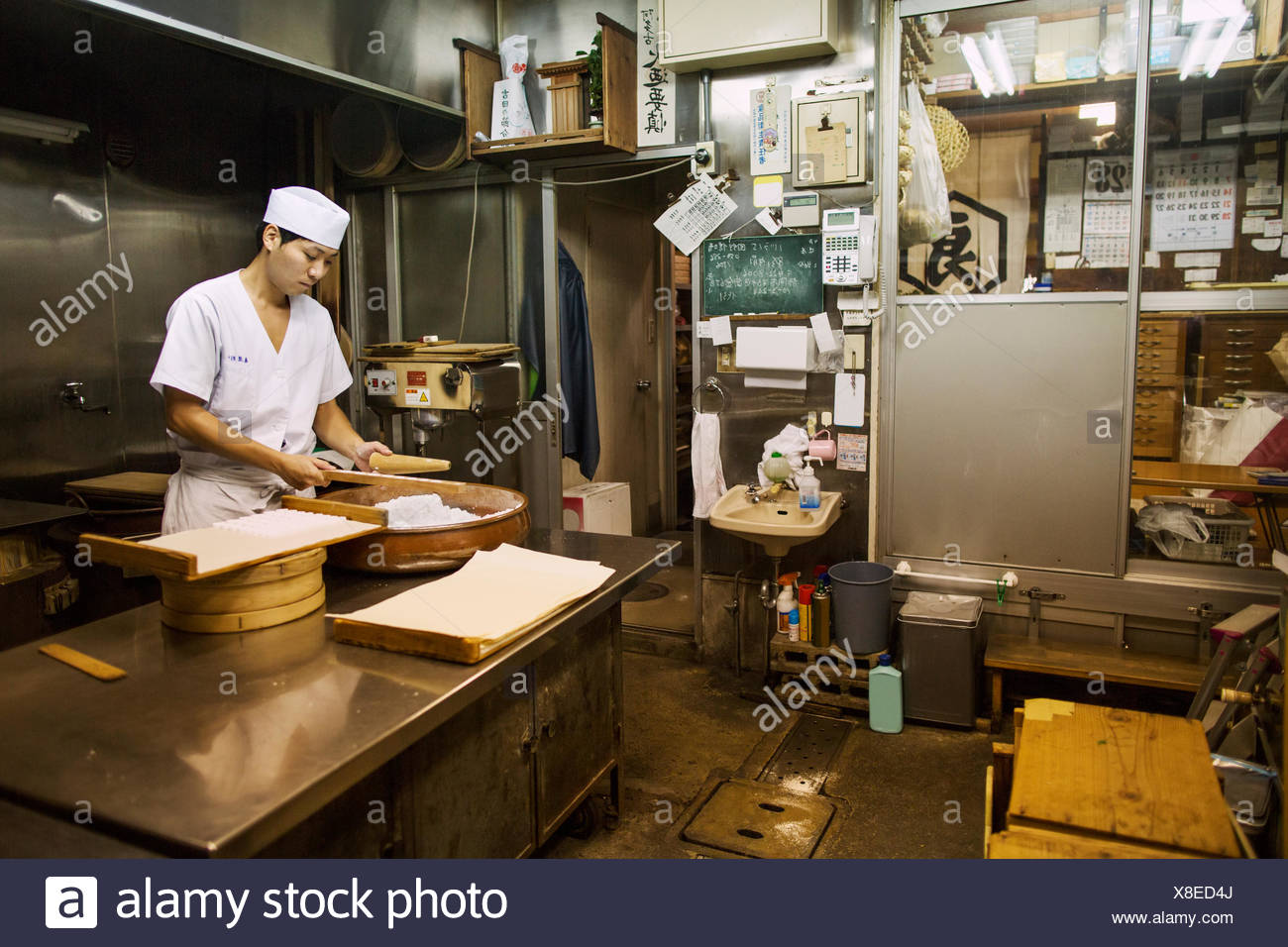 A small artisan producer of wagashi. A man mixing a large bowl of ingredients and pressing the mixed dough into moulds in a commercial kitchen. - Stock Image