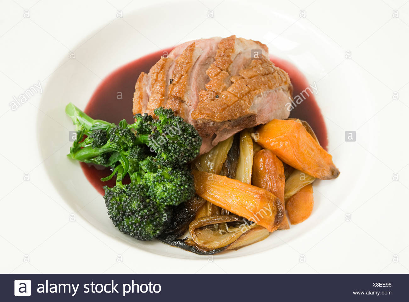 Roast duck with vegetables and jus - Stock Image