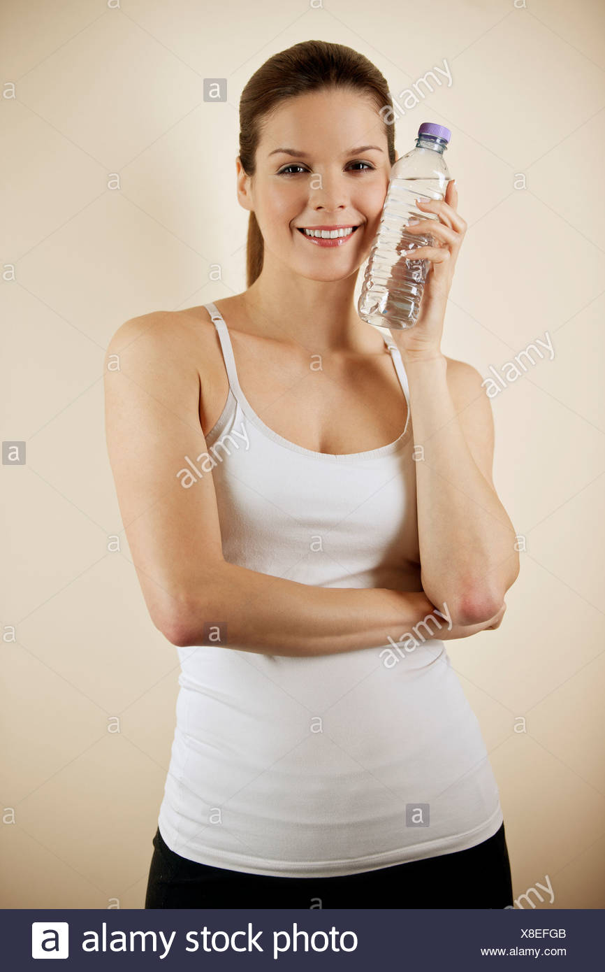 A young woman holding a bottle of water against her skin - Stock Image