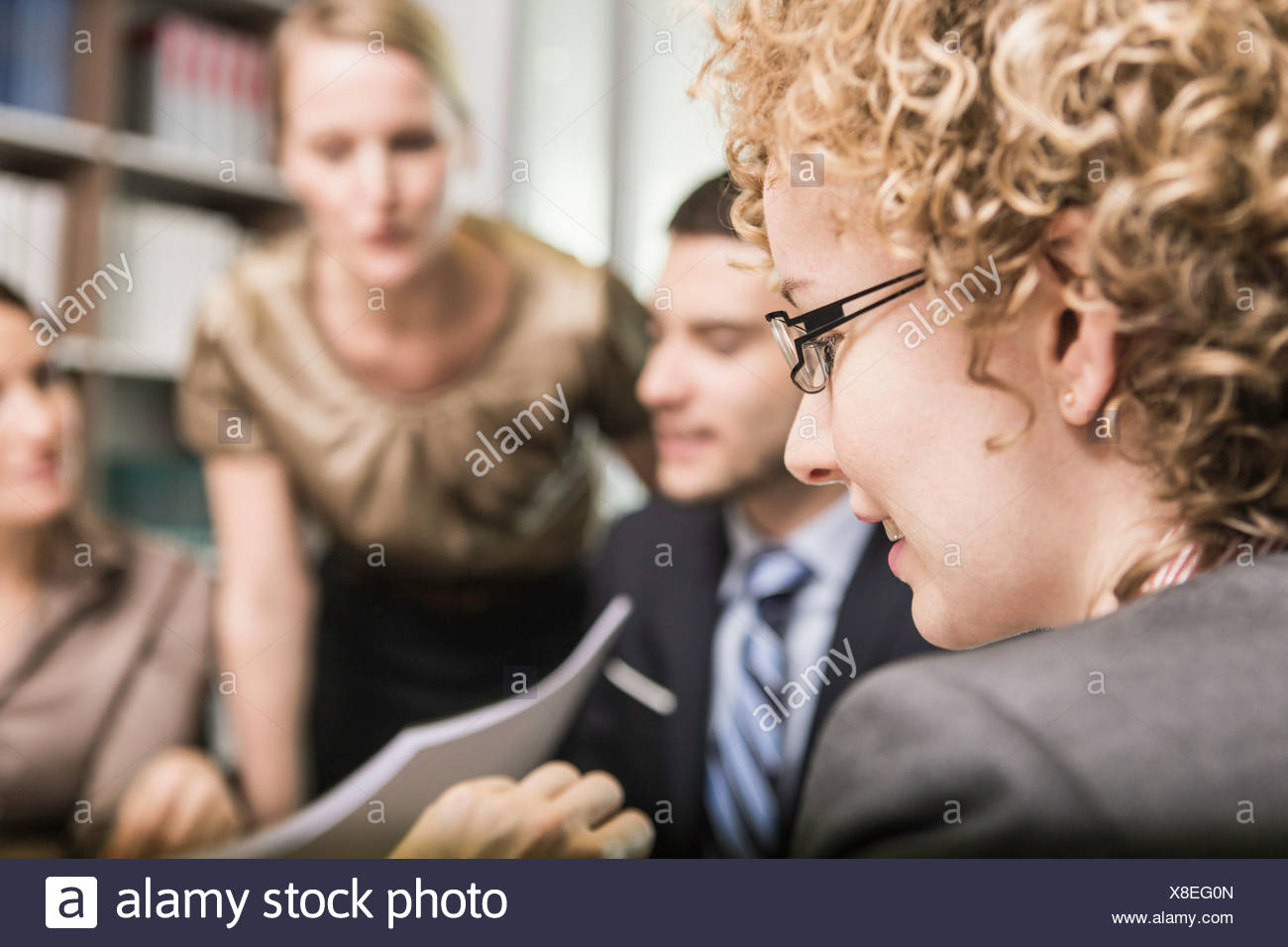 Female lawyer with blonde curly hair in meeting - Stock Image