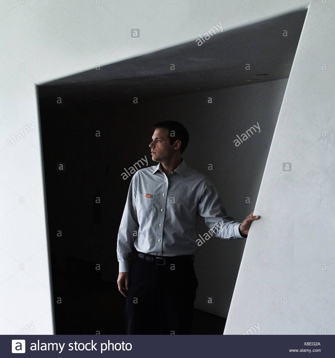 Young Man Looking Away Against Wall - Stock Image