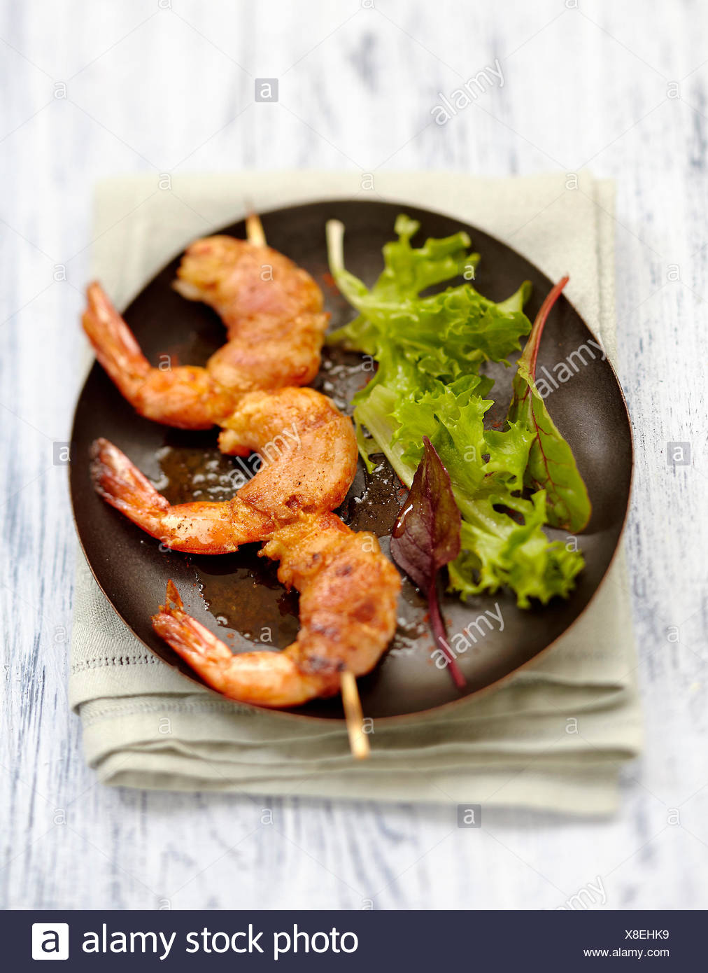 Gambas and bacon brochettes with mild pepper - Stock Image