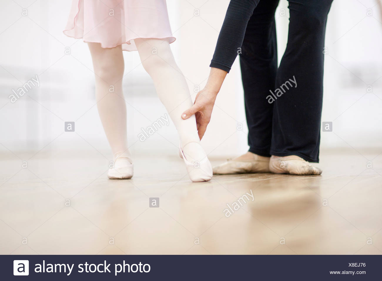 Close up of a young ballerina and teacher practicing toe point - Stock Image