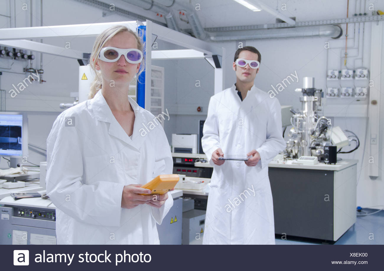 Two scientists wearing lab coats and safety glasses standing in laboratory - Stock Image