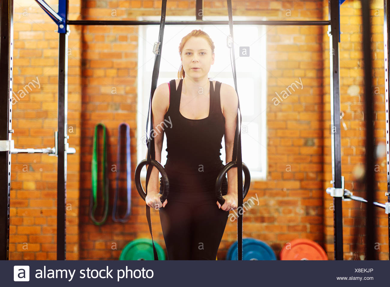 Woman pulling suspended rings in gym - Stock Image