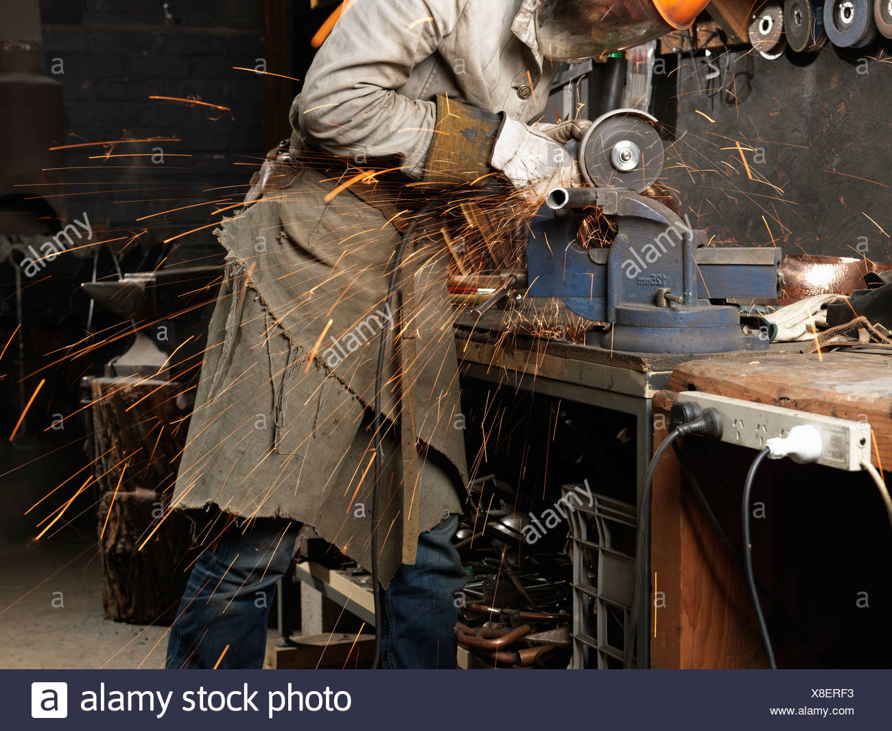 Blacksmith grinding metal on a machine in workshop - Stock Image