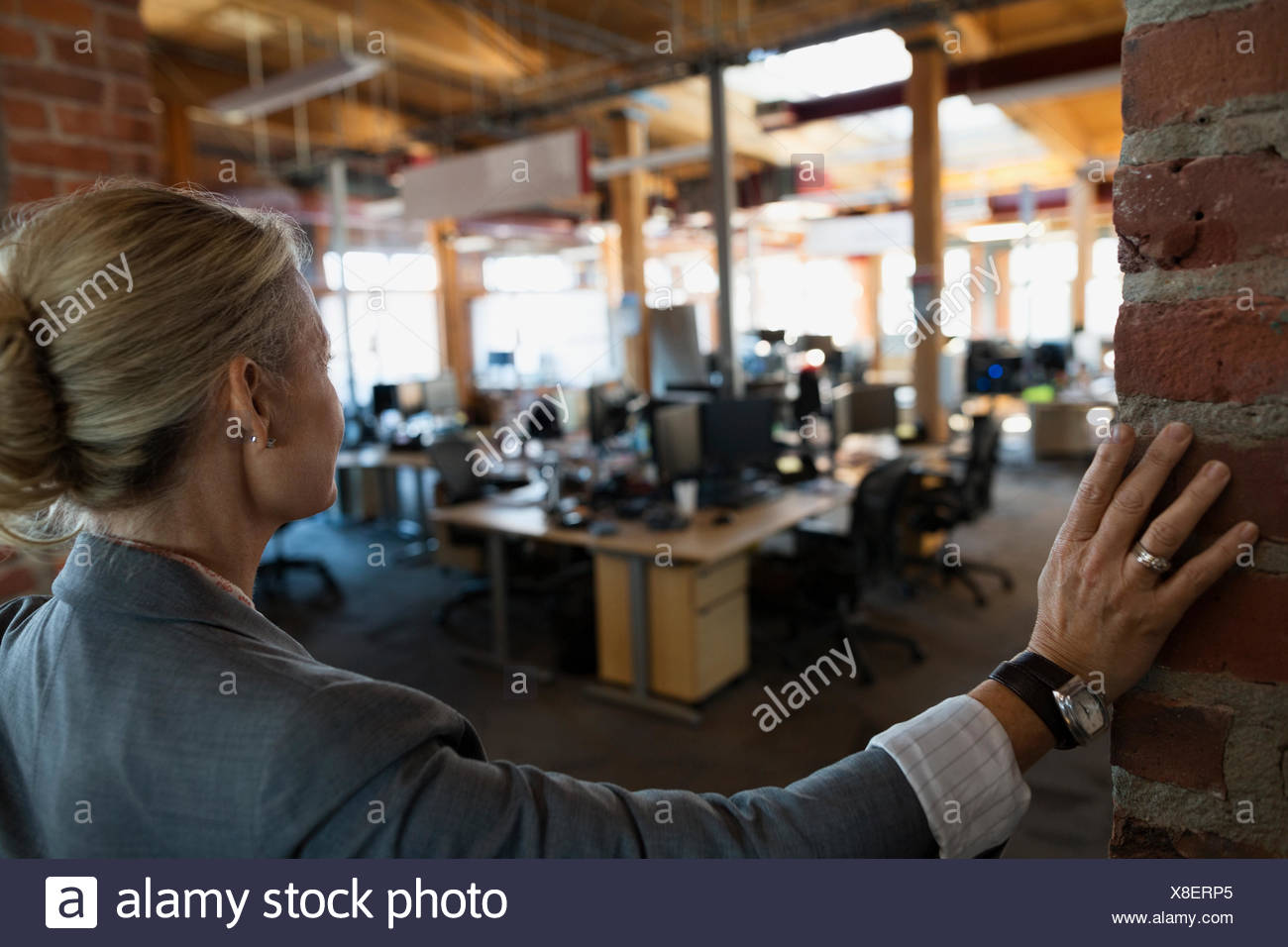 Businesswoman looking out at open office - Stock Image
