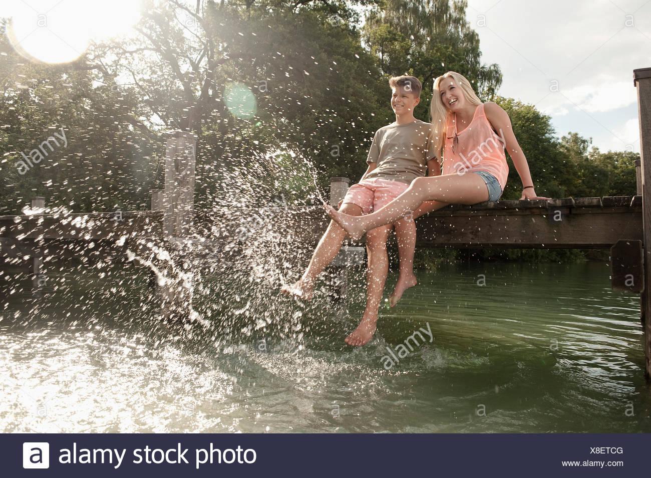 Teenage couple sitting on a jetty splashing water - Stock Image