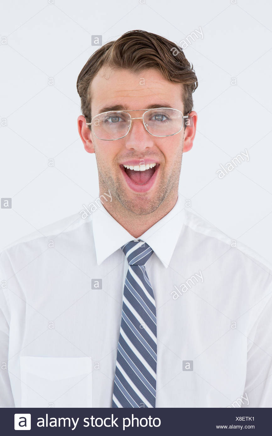 Happy geeky businessman looking at camera - Stock Image
