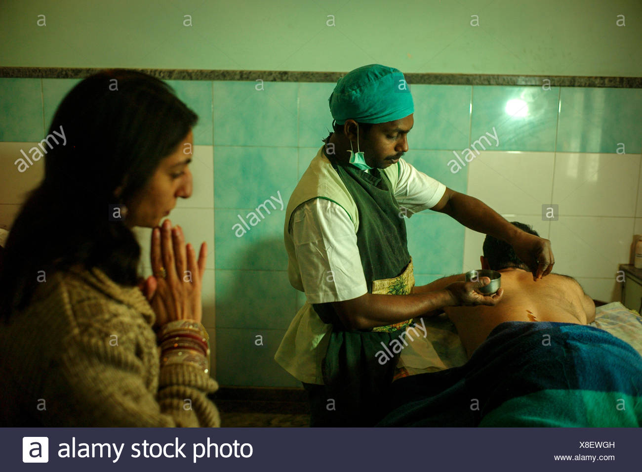 An Ayurvedic practitioner treats a patient for back pain using Patra Pinda Sweda Therapy at an Ayurvedic center, observed by a doctor. - Stock Image
