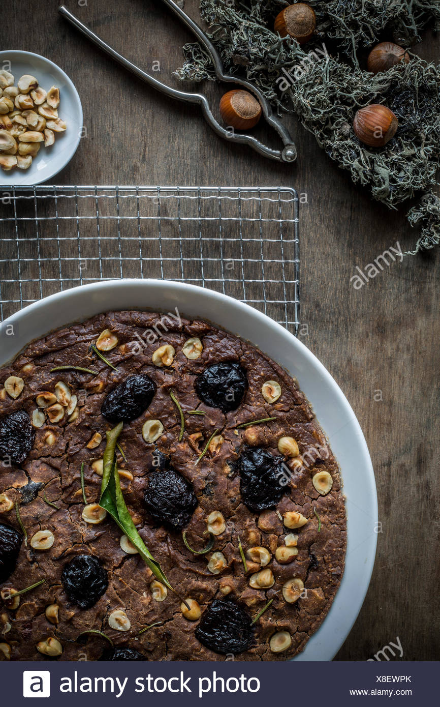 Festive Mediterranean Chestnut Flour Cake in white dish on cooling rack over wooden table top. Top view. - Stock Image