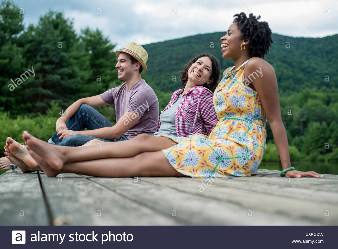 A group of people sitting on a woode pier overlooking a lake. Stock Photo