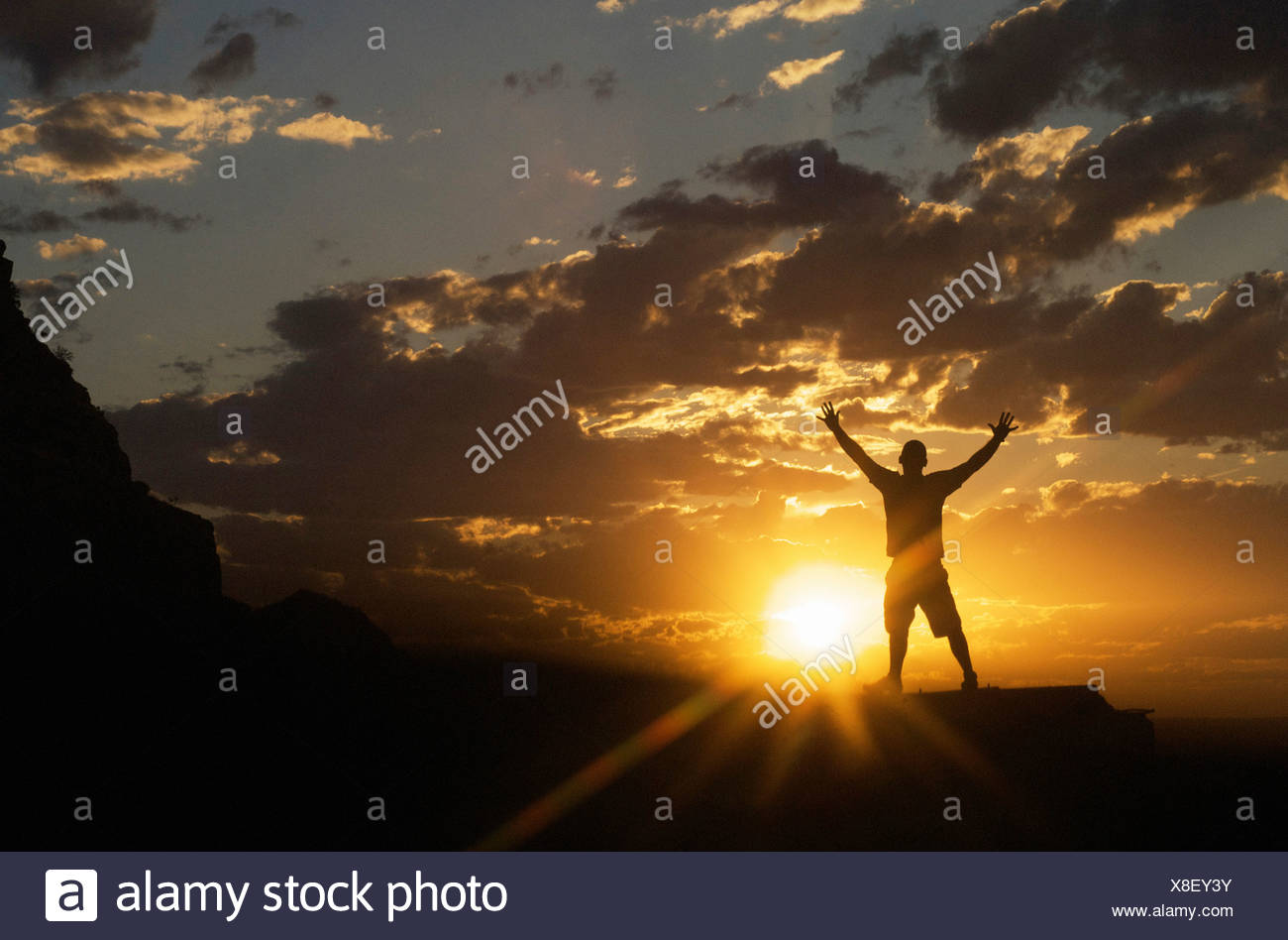 nature scenery and inspirational concepts: silhouette of man celebrating the dramatic sunset sky standing arms spread wide - Stock Image
