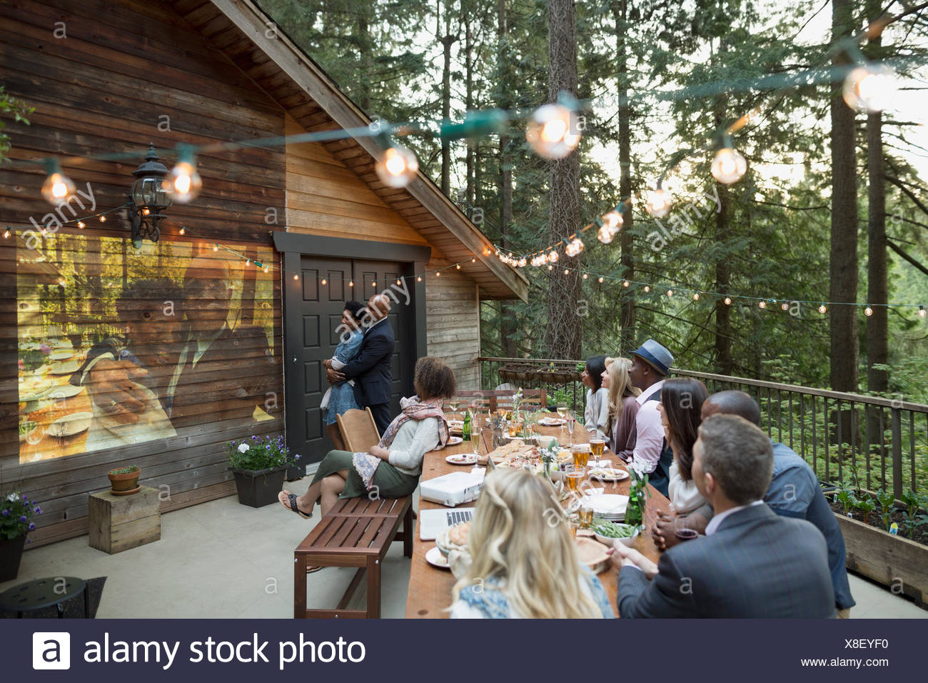 Friends watching projected slideshow at anniversary party on cabin balcony in woods - Stock Image
