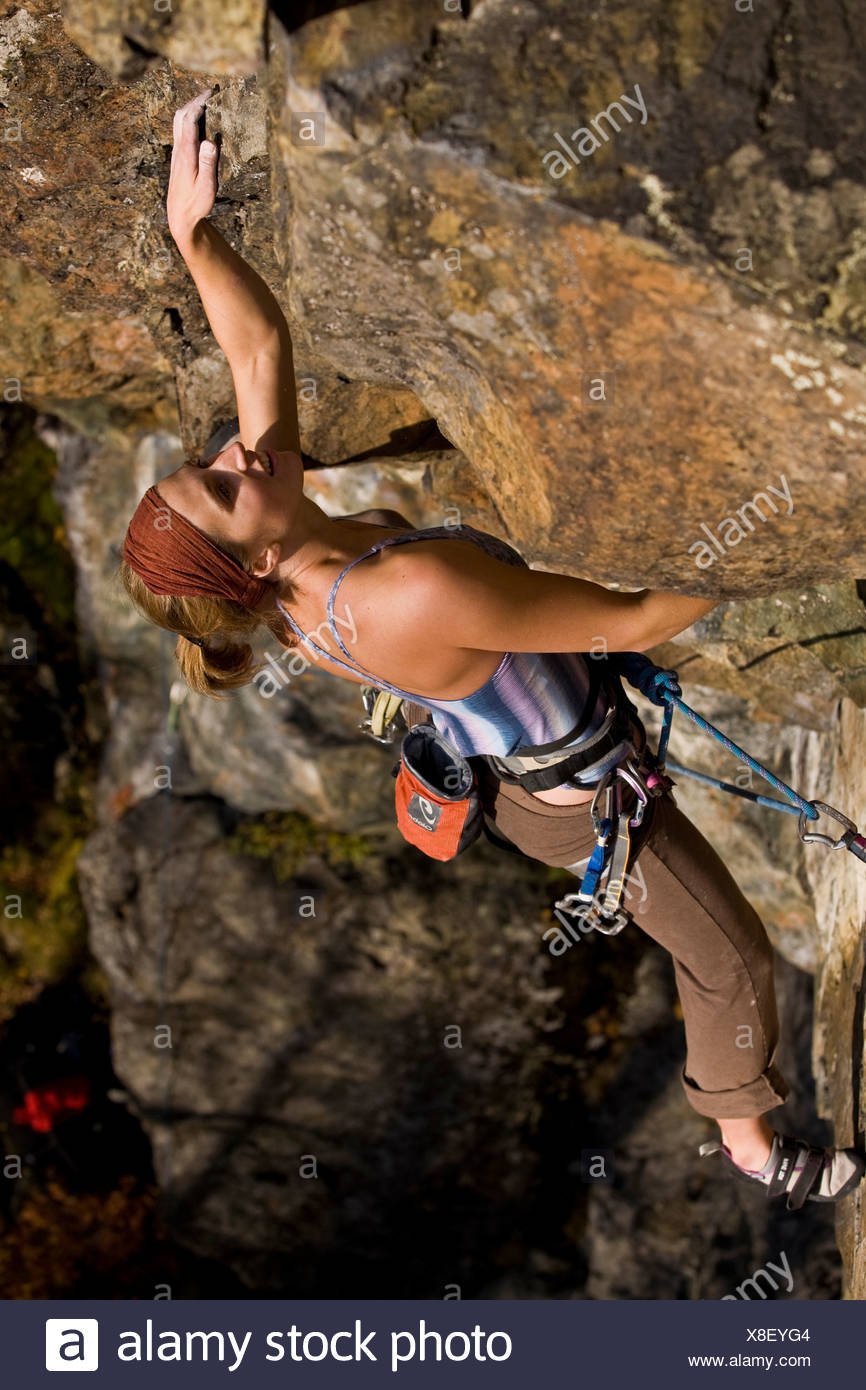 A young woman sport climbs Rechargeable Battery 5.11d, Mt. Orford, QC - Stock Image