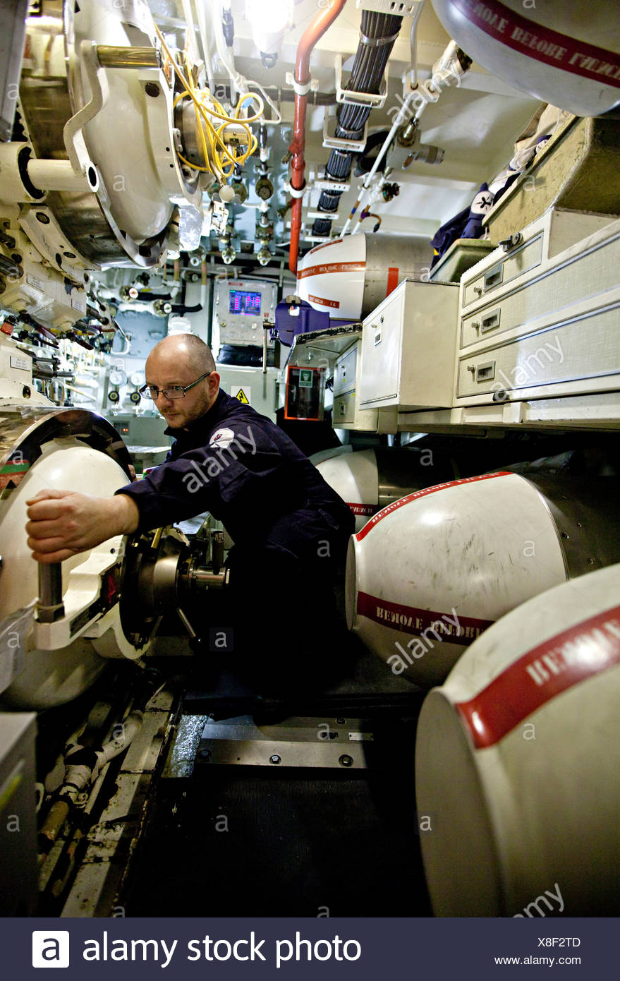 Crew man with hand on lever in torpedo room of Nuclear Submarine HMS Talent - Stock Image