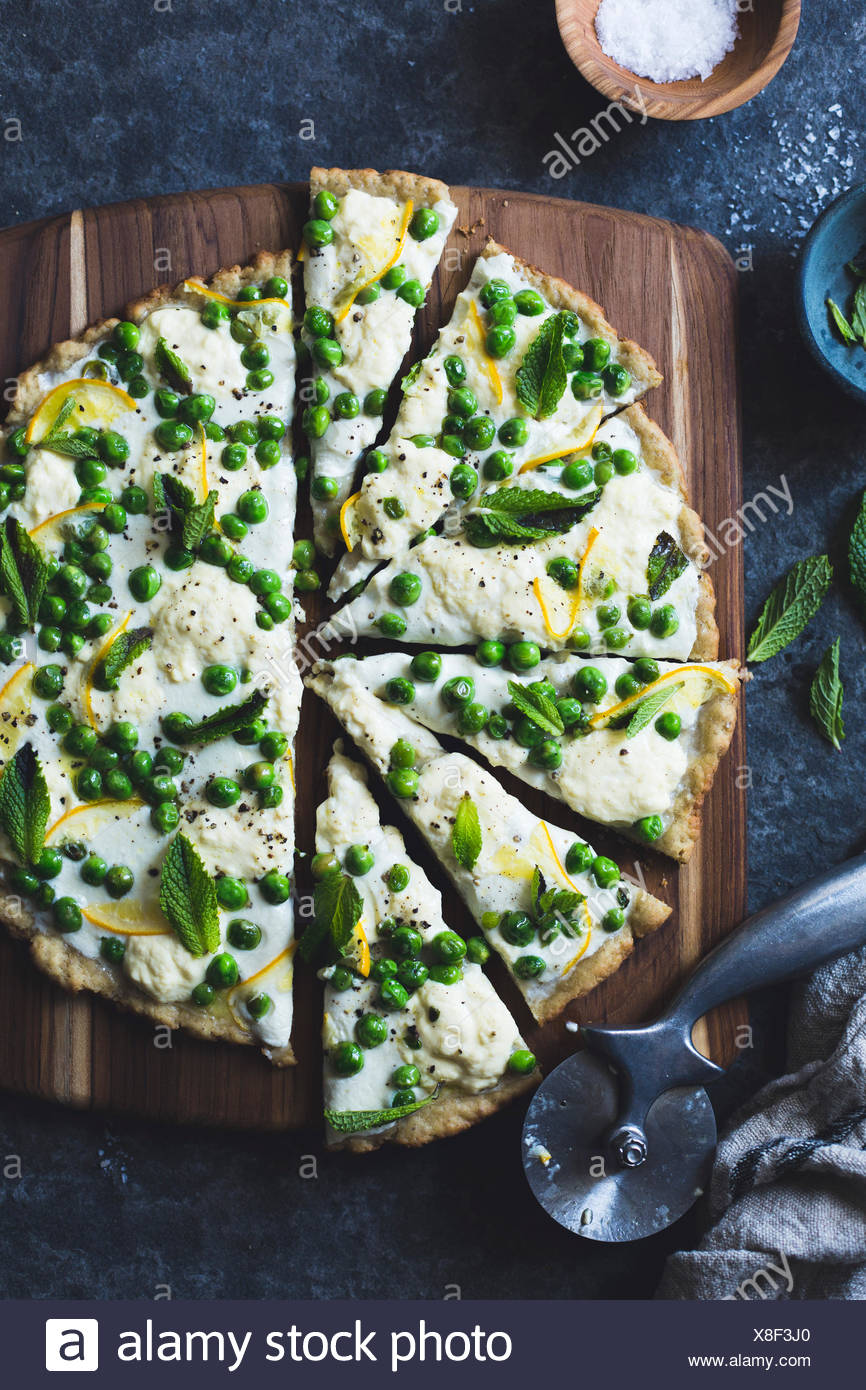 Thin and crisp grilled gluten-free pizza crust (whole grain + gluten-free) and a springy topping of fresh peas, meyer lemon, goa - Stock Image