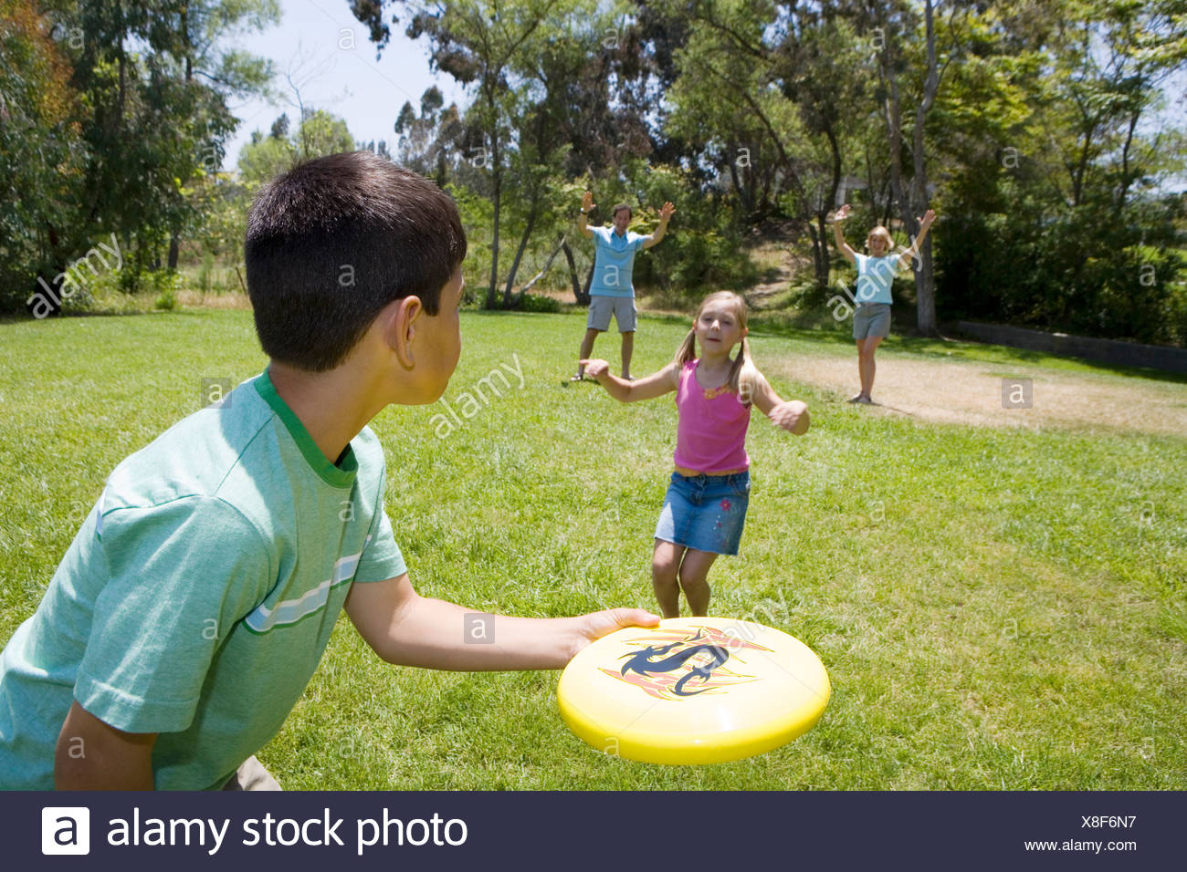 Family playing frisbee in park boy 9 11 throwing disc to parents girl 7 9 in middle - Stock Image