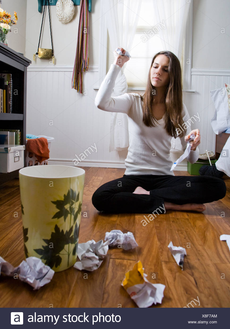 woman sitting on the floor throwing balls of paper into the wastebasket Stock Photo