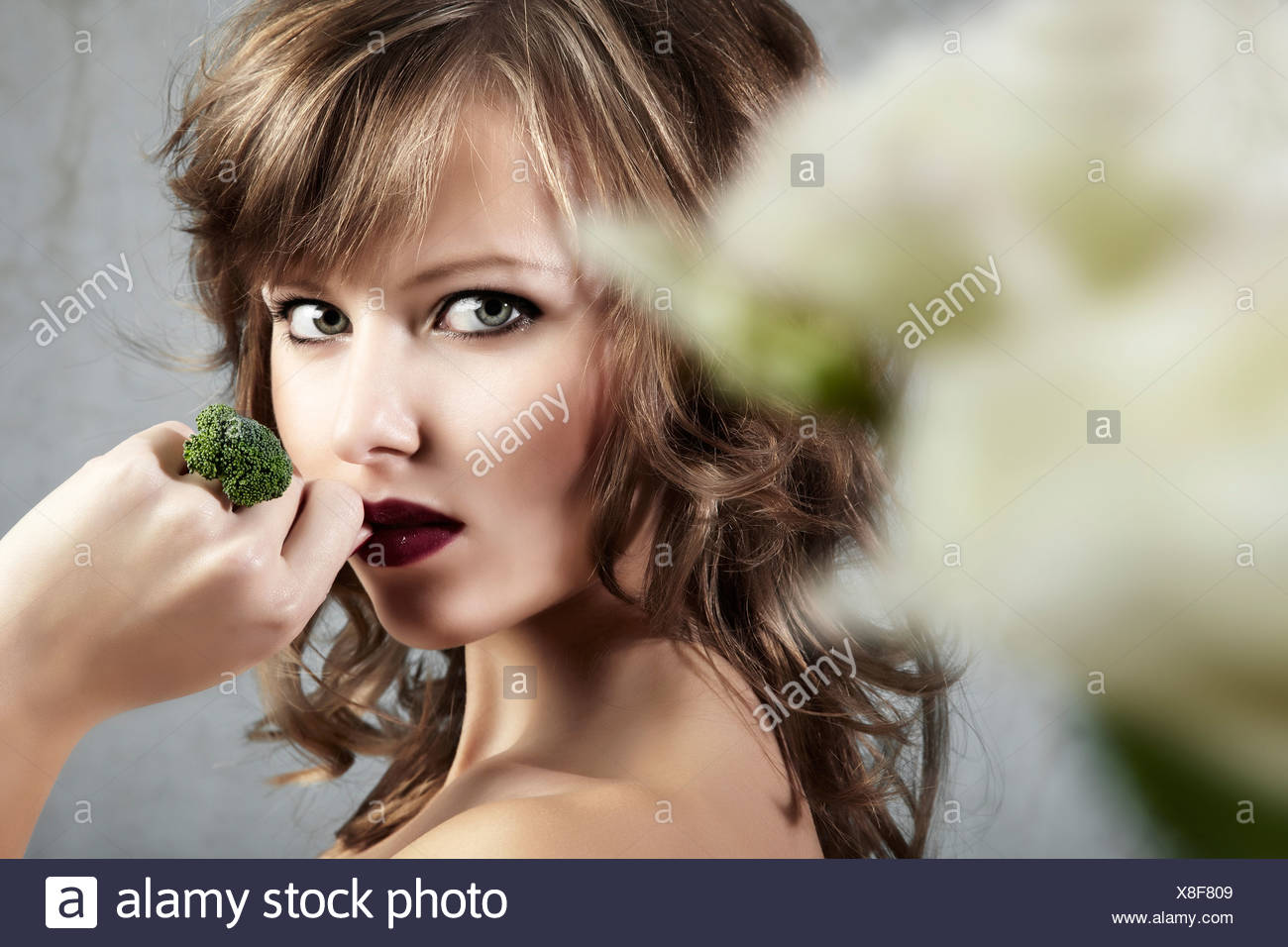 Side portrait of a young woman holding her hand with a broccoli ring seductively to her mouth, jewelry - Stock Image