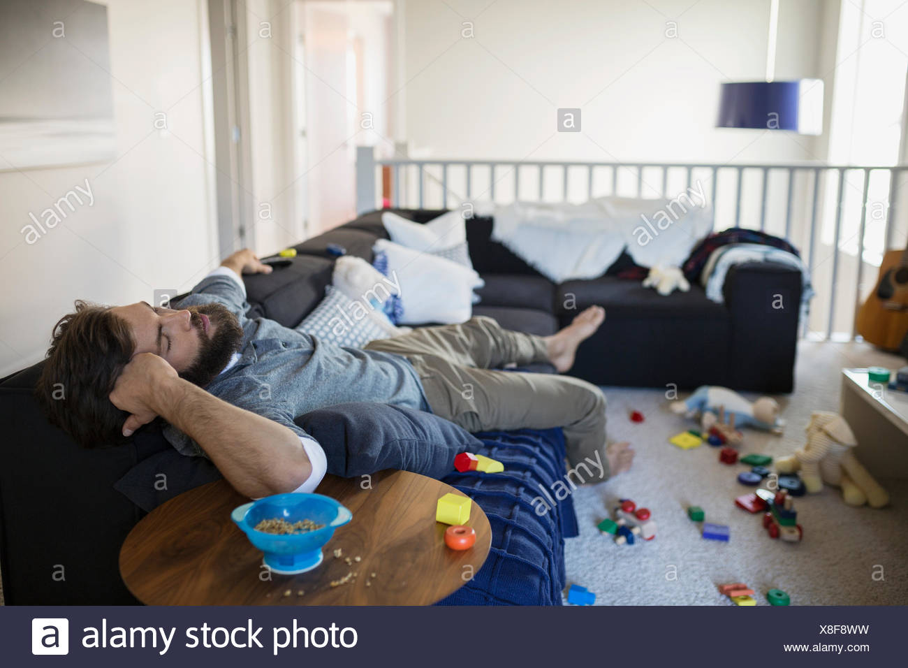 Exhausted man napping on sofa surrounded by toys - Stock Image