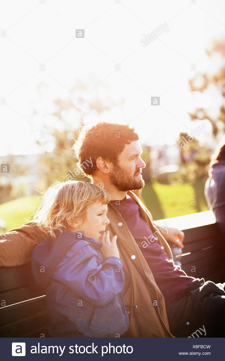 Sweden, Skane, Malmo, Vastra Hamnen, Father and son (6-7) sitting on park bench in sunlight - Stock Image