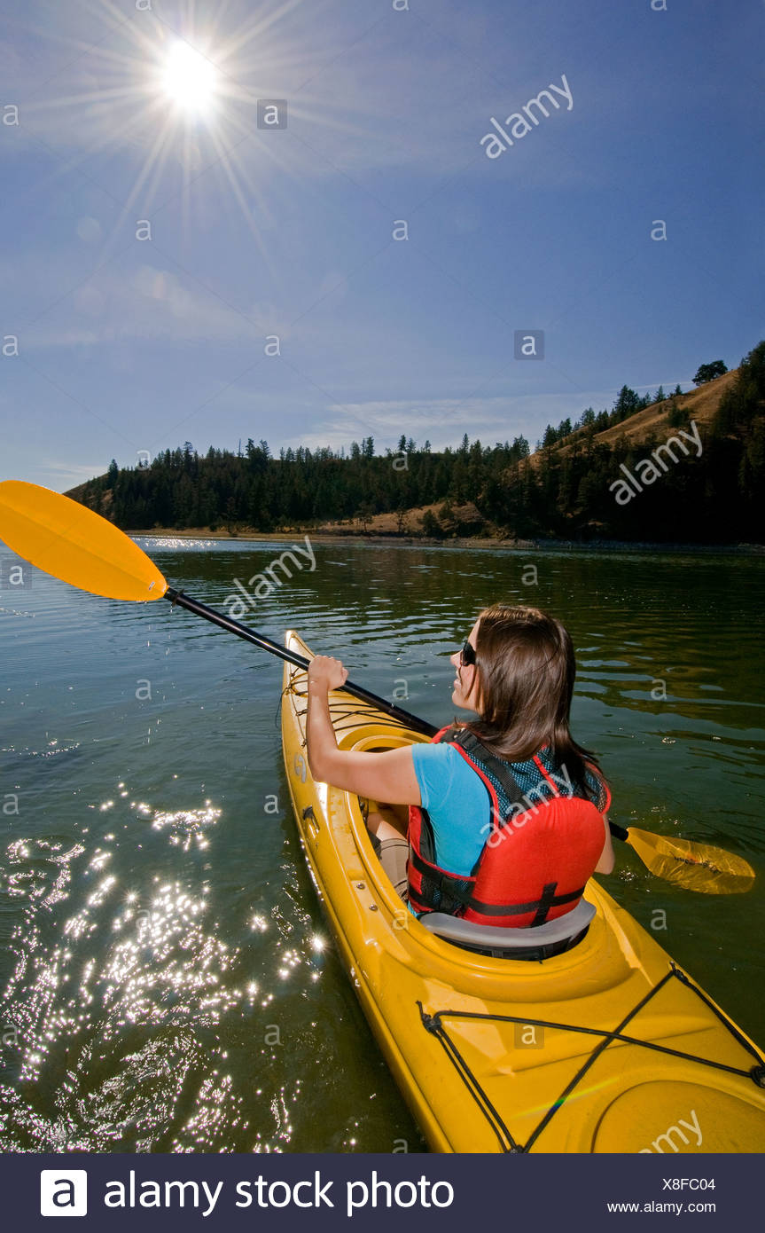 A young women enjoys a stunning day kayaking on Trapp Lake near Kamloops, British Columbia, Canada - Stock Image