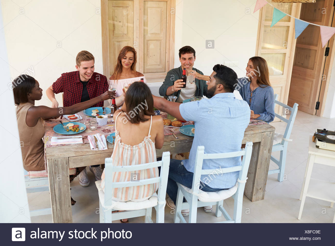 Friends making a toast at a dinner party on a patio, Ibiza - Stock Image