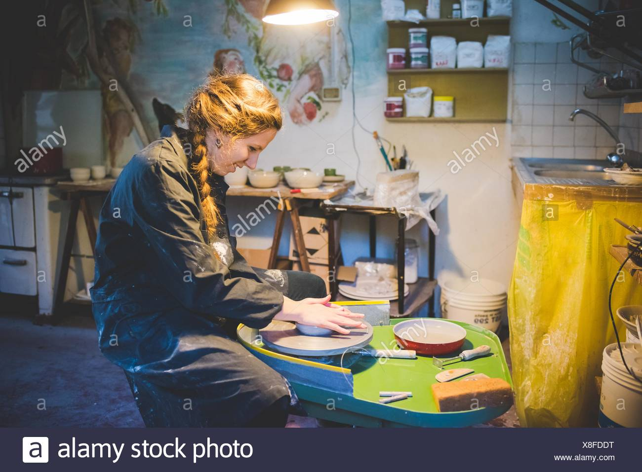 Side view of young woman sitting in workshop using potters wheel, looking down smiling - Stock Image