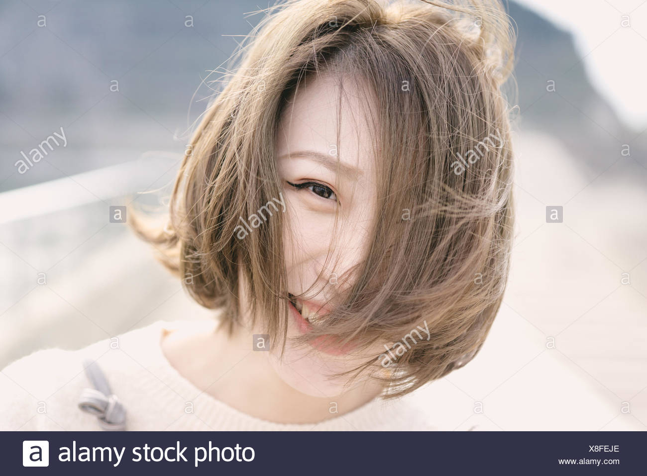 Portrait Of Happy Young Woman At Lakeshore - Stock Image