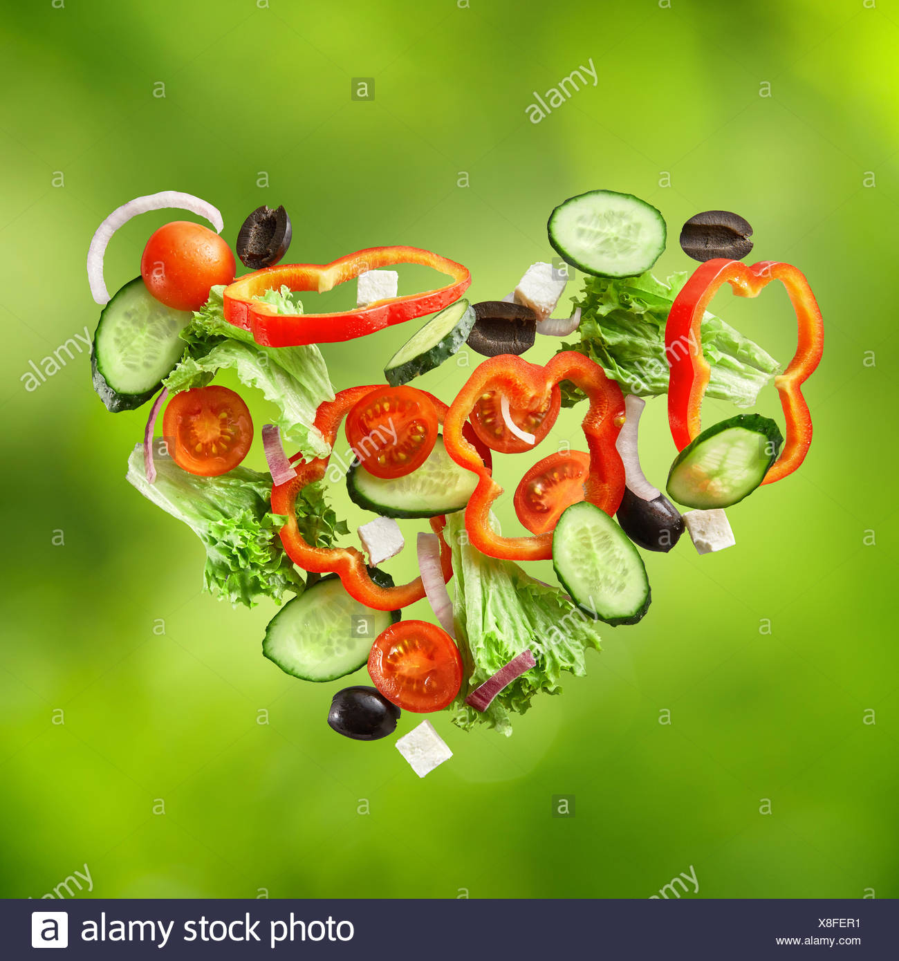 flying salad on natural green background - Stock Image