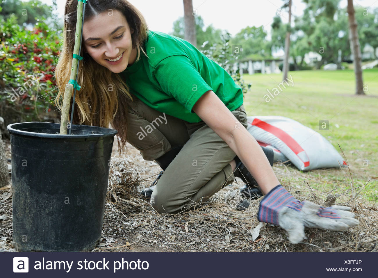 Happy female environmentalist cleaning up after planting at park - Stock Image