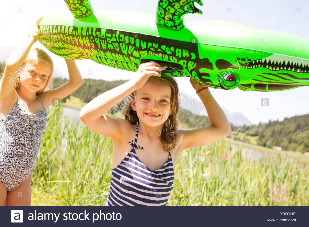 Two young girls walking through field, carrying inflatable crocodile Stock Photo