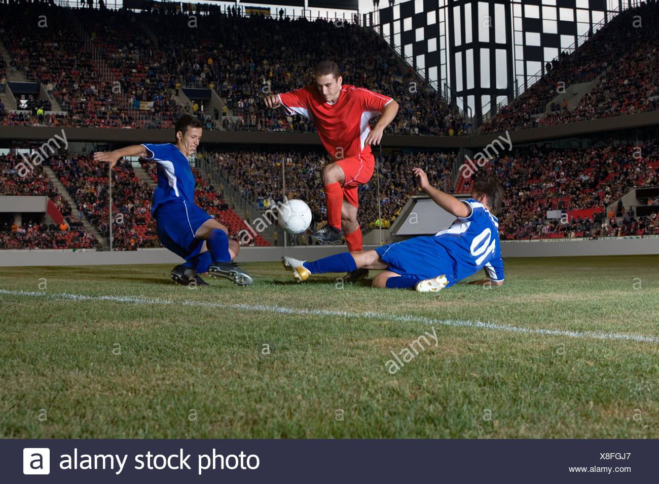 Opposite players tackling footballer - Stock Image