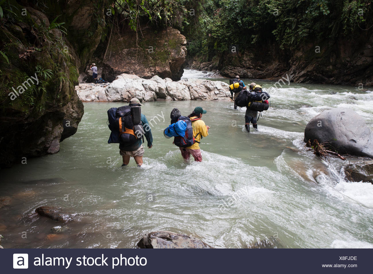 People cross a river on a trek into the reserve managed by the Queros Wachiperi indigenous community. - Stock Image