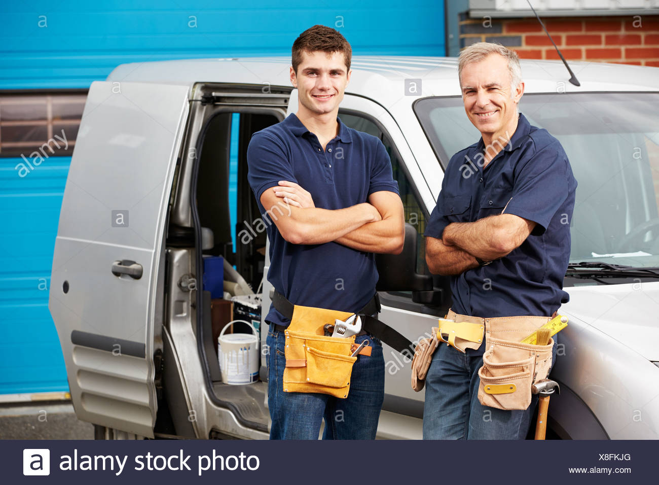 Workers In Family Business Standing Next To Van - Stock Image