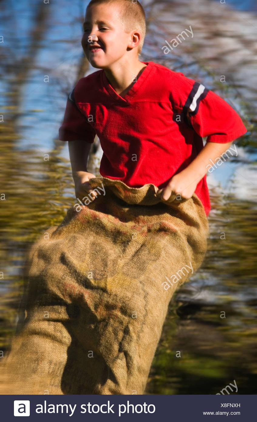 Boy having a gunny sack race - Stock Image