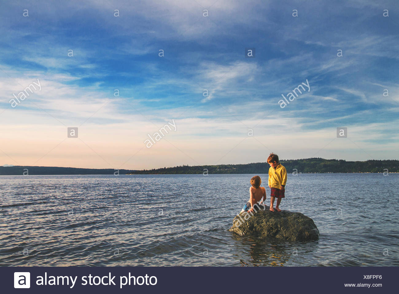 Two boys sitting on a rock in the sea - Stock Image