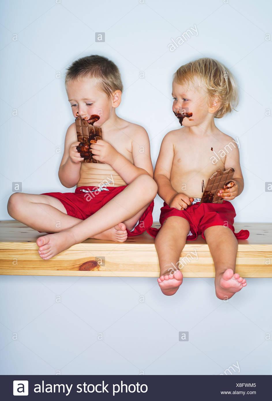 Portrait of boys (2-3), (4-5) eating chocolate - Stock Image