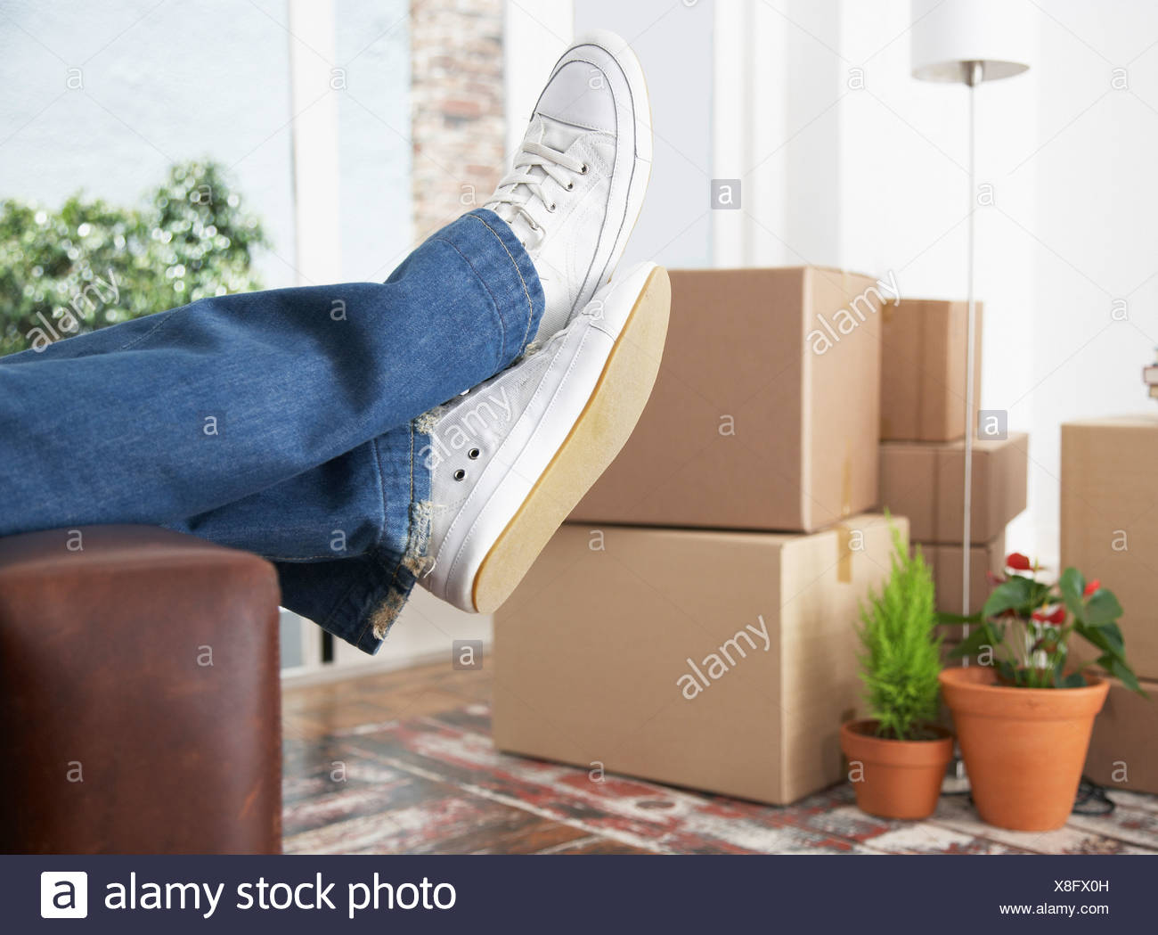 Man lying down on sofa in home with cardboard boxes - Stock Image