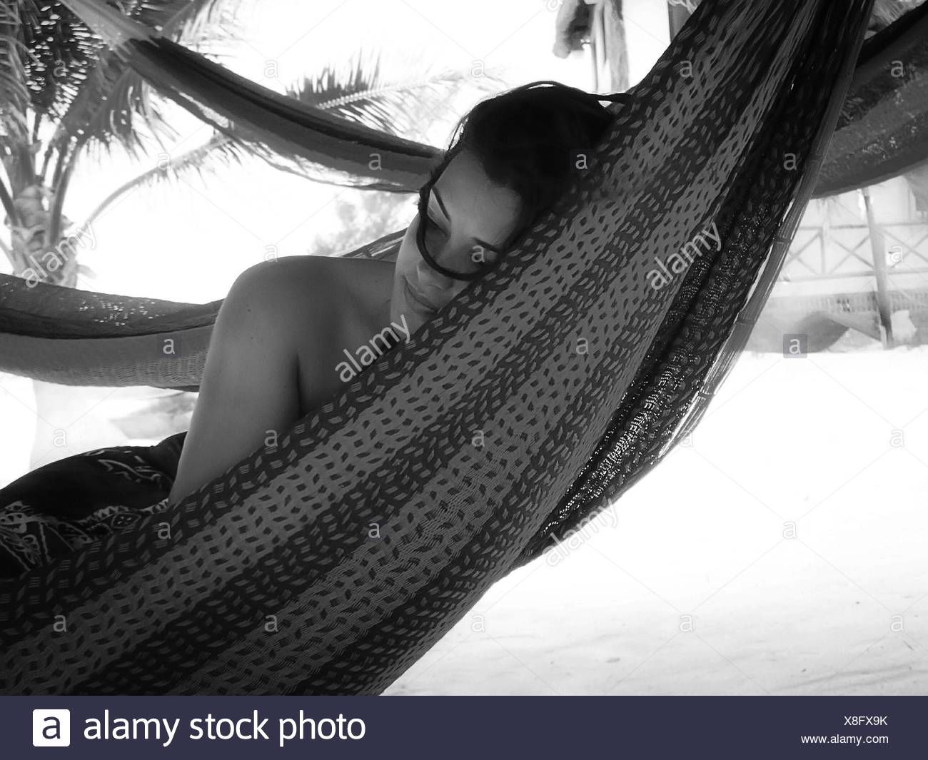 Woman Relaxing In Hammock At Beach - Stock Image