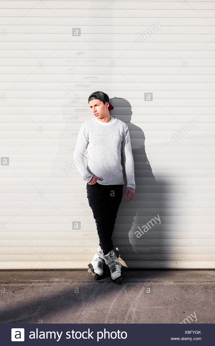 Young man with inline skates standing on manhole cover - Stock Image