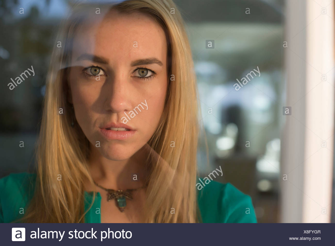 Portrait of young woman staring through window - Stock Image