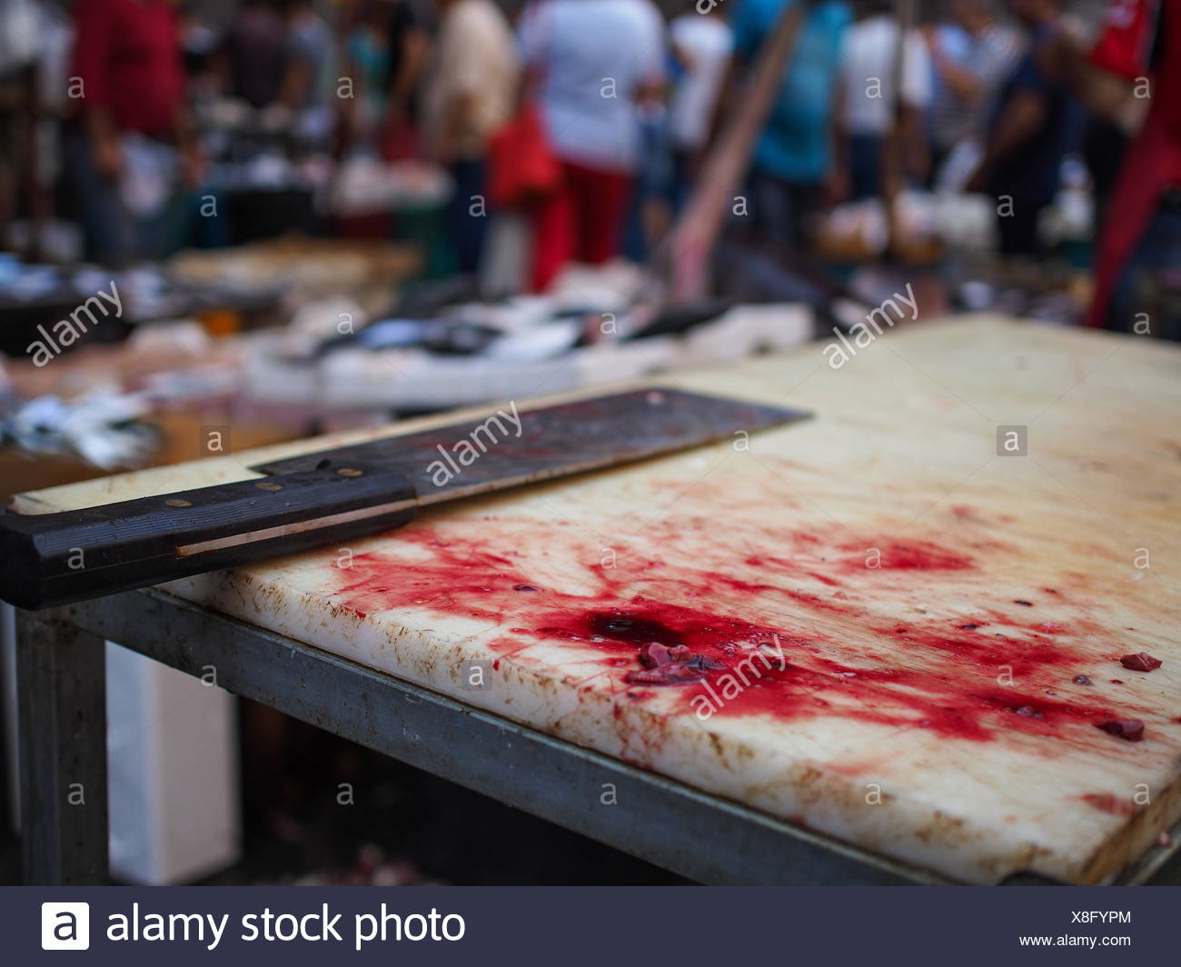 Close-Up Of Meat Cleaver With Blood On Cutting Board At Fish Market - Stock Image