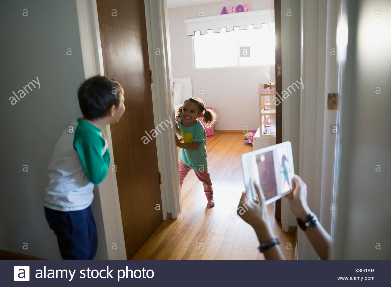 Mother photographing brother and sister playing in corridor - Stock Image