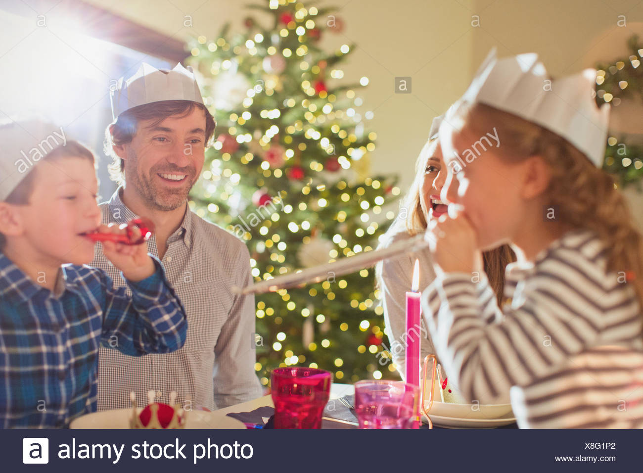 95fe2321504bc Family wearing paper crowns at Christmas dinner table Stock Photo ...