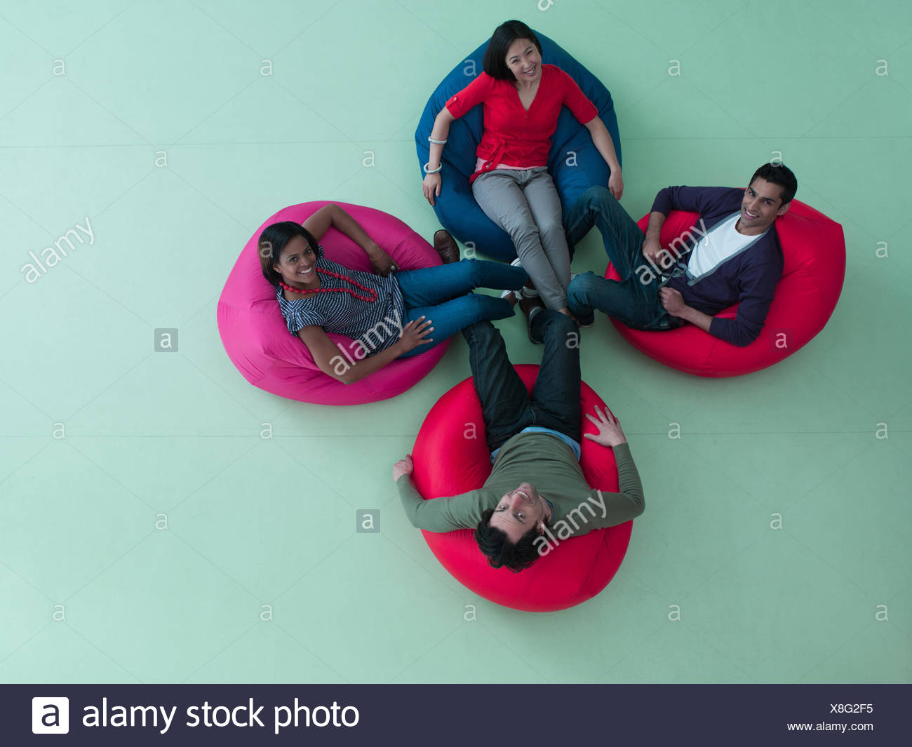 Smiling men and women  bean bag chairs - Stock Image